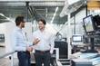 Two businessmen talking in modern factory