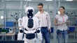 Human-like robot is getting switched on by a male engineer who is then telling something to a female one