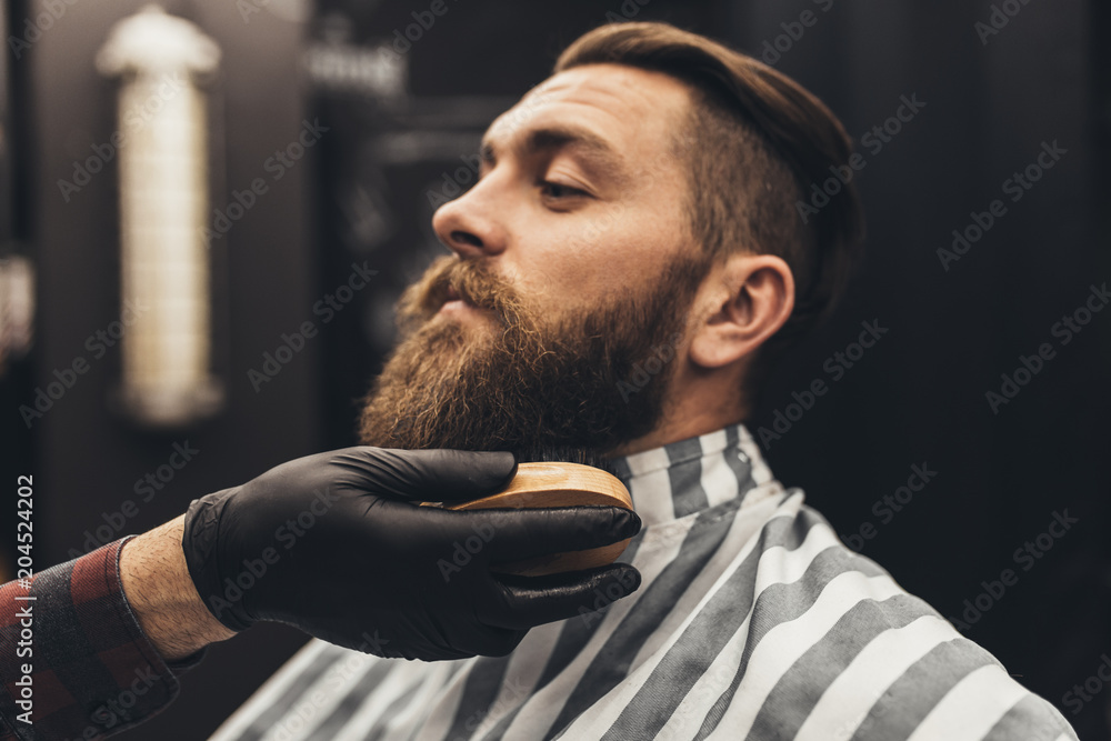Fototapeta Hipster young good looking man visiting barber shop. Trendy and stylish beard styling and cut.