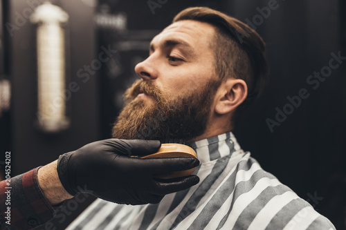 Hipster young good looking man visiting barber shop. Trendy and stylish beard styling and cut.