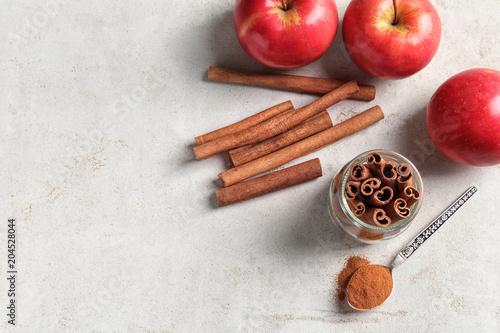 Fototapeta Fresh apples with cinnamon sticks and powder on table, top view obraz