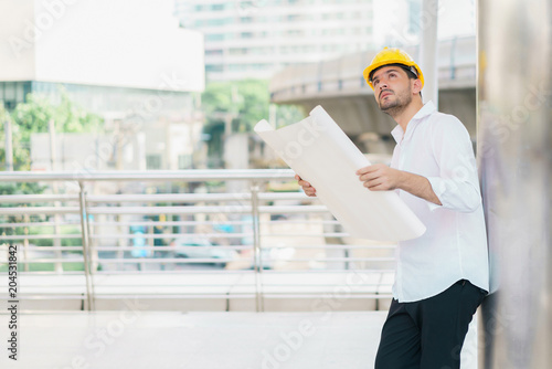 Engineer man wearing safety helmet and hold blueprint document at engineer man wearing safety helmet and hold blueprint document at construction site concept of work malvernweather Gallery