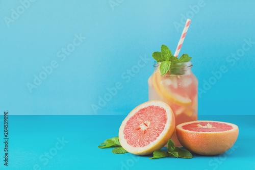 Carta da parati Jar with grapefruit lemonade, decorated ice and mint on blue paper background