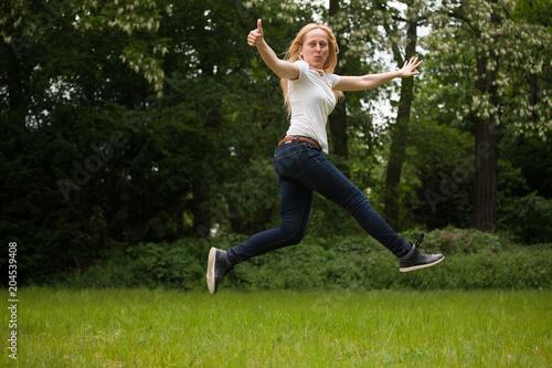 Photo Woman jumping, ok sign.