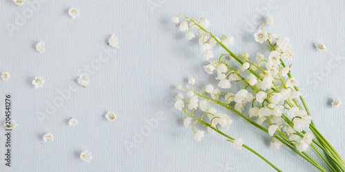 Poster Lelietje van dalen Lily of the valley on a blue paper textured background. Pattern of small flowers of the may-lily. Abstract floral background.Top view, flat lay. March 8, mother's day background.