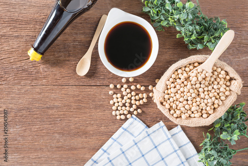 Soy bean with Soy sauce in bowl and bottle on wood background.