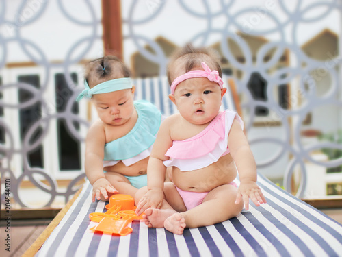 Cute Twin Baby In Swimsuit On Sun Loungers Buy This Stock Photo