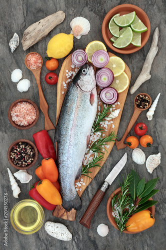 Healthy heart food with rainbow trout fish, seasoning, herbs, vegetables and olive oil on marble background. High in omega 3 fatty acids.