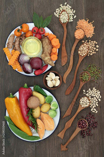 Poster Assortiment Health food selection with fresh vegetables, fruit, herbs, spice, dried pulses and olive oil on rustic oak background. Super food concept with foods high in antioxidants and vitamins.
