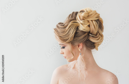 Beautiful young woman with a trendy blonde hairstyle, head and shoulders portrait on a grey studio background