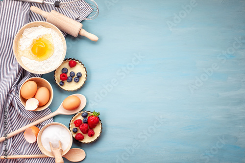 Fototapeta Baking utensils and cooking ingredients for tarts, cookies, dough and pastry. Flat lay with eggs, flour, sugar, berries.Top view, mockup for recipe, culinary classes, cooking blog. obraz