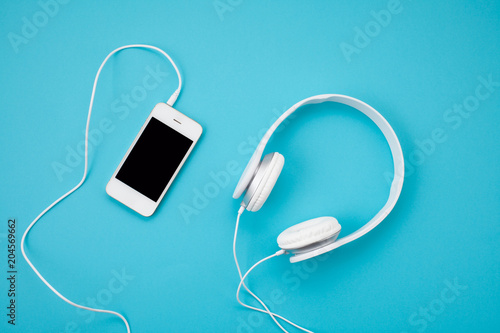 Fototapeta Top view of white earphones with smartphone on blue background. Online music concept obraz na płótnie
