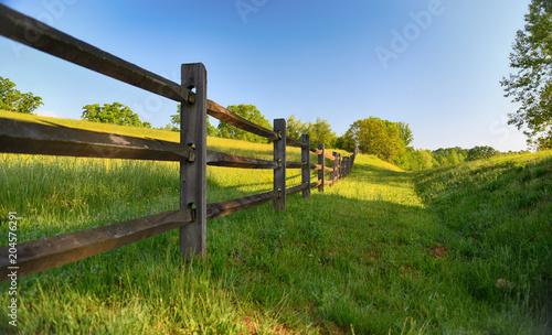 "Fotografia, Obraz ""The Fence"" americana series a rustic wood fence runs along a lush green pasture"