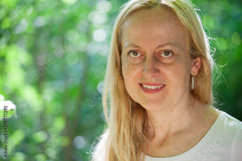Smiling blond woman relaxing outdoor Fototapet
