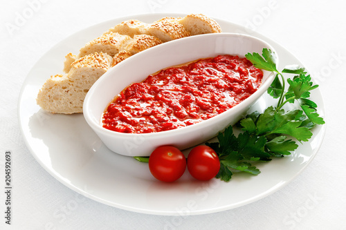 Fototapeta ajvar appetizer served with white bread, cherry tomatoes, and parsley obraz