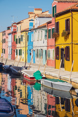 Fototapeta na wymiar Colorful houses, water canal and boats in Burano, Venice