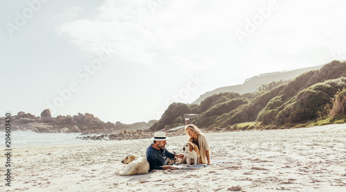 Papiers peints Voile Senior couple relaxing on beach with pet dogs