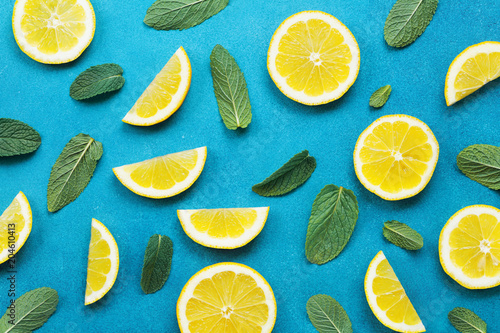 Punchy pastel background with lemon slices and mint leaves. Summer colorful pattern. Flat lay style.