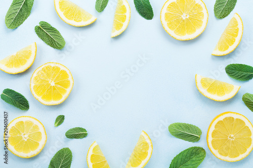 Fotografia Frame from lemon slices and mint leaves on blue pastel table top view