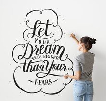 Female Artist Writing A Life Motivation Quote On The Wall