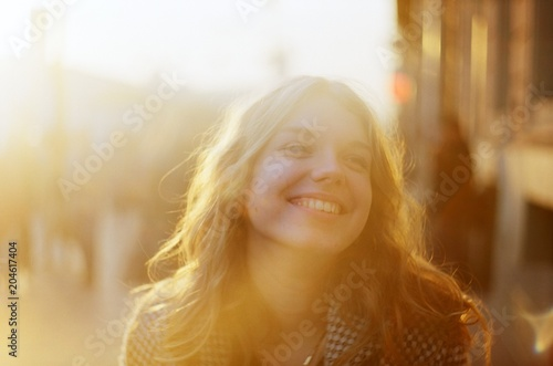 Fotografia, Obraz  Blonde woman with a beautiful beaming smile backlit by the warm glow of the sun