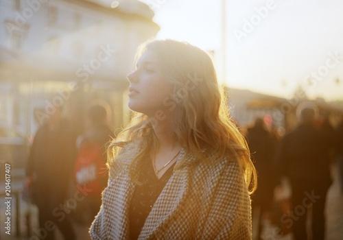 Fotografia  Beautiful young blonde woman enjoys sun beams at crowdy city street