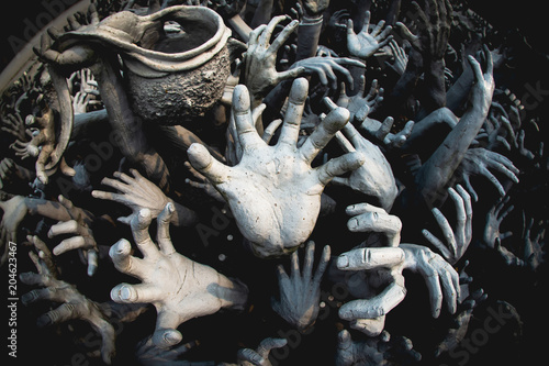 Photographie A statue of a hand that emerges from the ground, represents the abstract of good doing, and hell and heaven