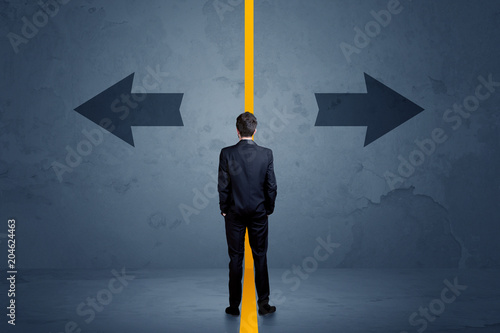 Photo  Business person choosing between two options separated by a yellow border arrow