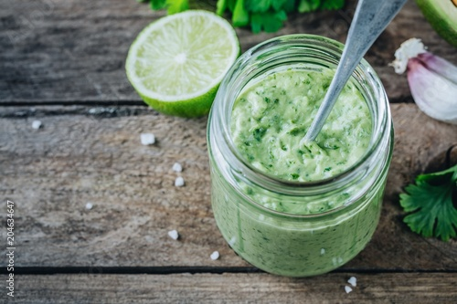 Fotografie, Obraz green salad dressing with avocado, lime and cilantro in a glass jar