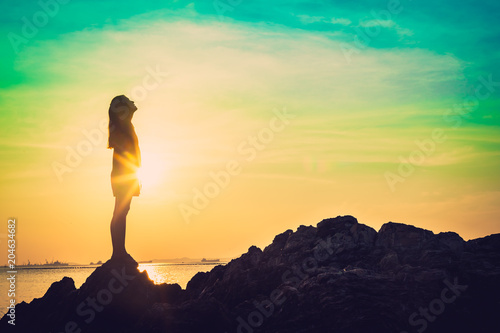 Silhouette of young woman relax pose or freedom pose or chill pose and standing at on the beach during sunset.