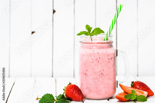 Fruit smoothie with strawberries, milkshake with fresh strawberry blended in jar on white background