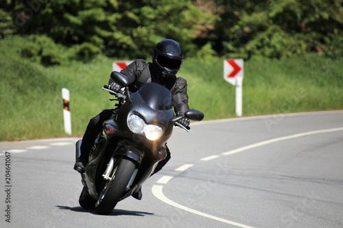 Motorradfahrer auf einer kurvenreichen Landstraße
