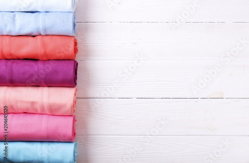 Fényképezés  Close up of colorful clothes neatly rolled for saving luggage space, stack of cotton t-shirt rolls of different pastel colors on wooden texture table