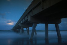 North Side Of Deerfield Beach, Florida Pier At Twilight With Moonrise Partially Obscured By Clouds In A Long Time-Exposure With Foggy Cotton Candy Waves At The Base In Late October Near Halloween