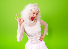 Portrait Of Funny Girl In Blonde Wig Show OK. Studio Shot.