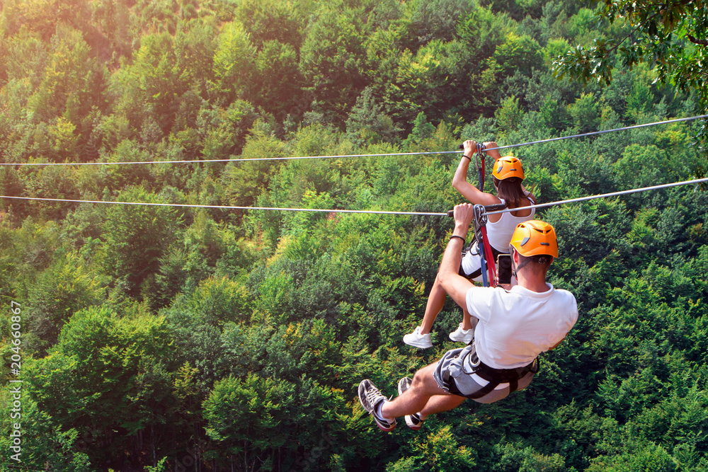 Fototapety, obrazy: Zipline is an exciting adventure activity. Man and woman hanging on a rope-way. Tourists ride on the Zipline through the canyon of the Tara River Montenegro. Couple in helmets is riding on a cable car