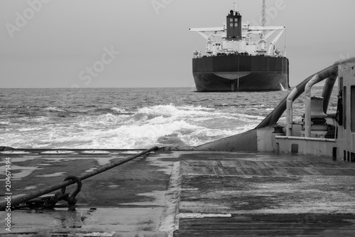 Fotografie, Obraz  BW black and white view of Anchor-handling Tug Supply AHTS vessel during dynamic positioning DP operations with FPSO tanker
