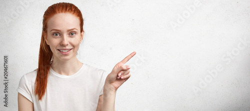 Fotografie, Obraz  Horizontal portrait of cheerful redhead European woman with pony tail and freckl