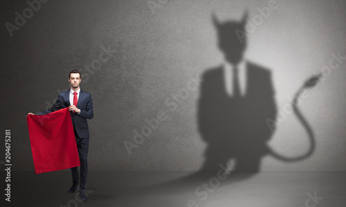 Fotografiet Businessman standing with red cloth in his hand and devil shadow on the backgrou