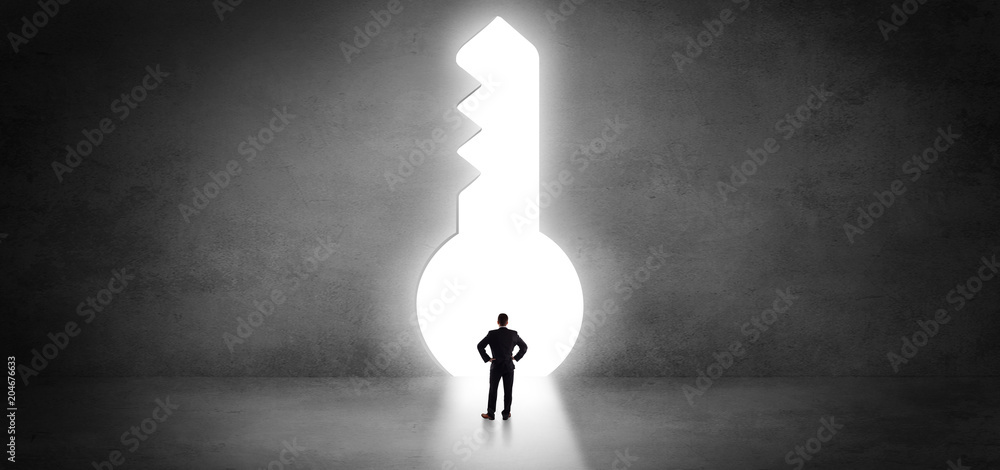 Fototapeta Businessman standing alone in front of a big keyhole