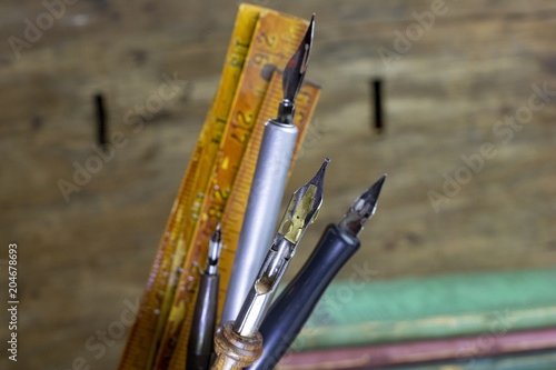 A pencil cup with lots of vintage pens and a vintage slide