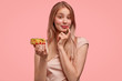 Charming young lovely female holds sweet doughnut, proposes you to eat delicious dessert, can`t refuse tasty eating, isolated over pink background. Gorgeous cute woman with donut. Junk food.