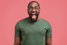Studio Shot Of Mad African American Male Screams Angrily At Someone, Being Irritated, Wears Casual T Shirt, Isolated On Pink Background. Irritated Man Boss Shouts In Despair. Crazy Dark Skinned Guy