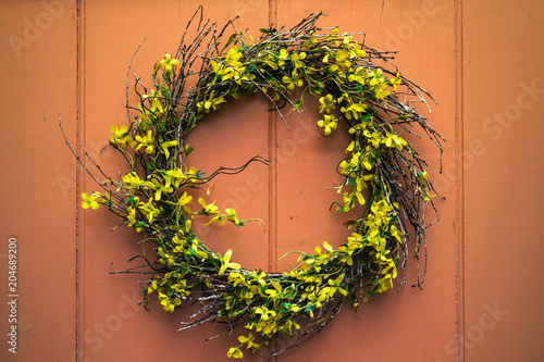 A yellow forsythia wreath hangs on an old wooden door, with dappled sun and shade playing across its surface Wallpaper Mural