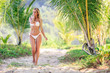 Woman in white bikini walking between palm trees at the tropical beach