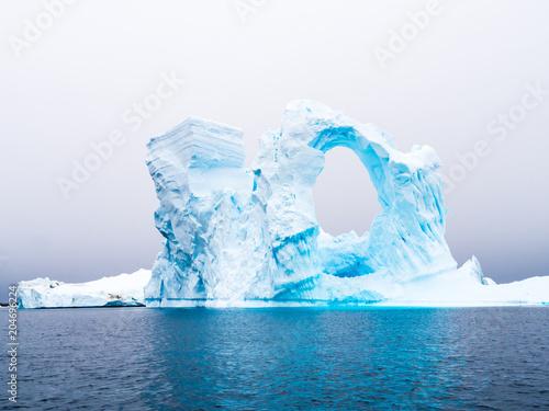 Arch shaped iceberg in Pleneau Bay iceberg graveyard west of Antarctic Peninsula Canvas Print
