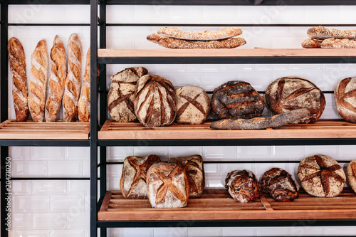Foto op Canvas Brood Close up many freshly baked bread on the shelf such as nuage, baguette and spelt bread.