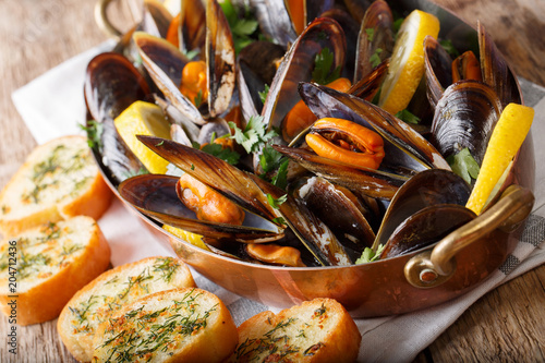 Fotobehang Schaaldieren Cooked mussels with lemon, parsley and garlic macro in a saucepan. horizontal
