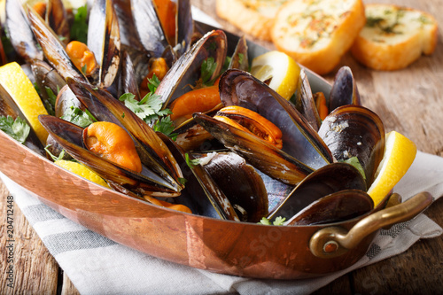 Fotobehang Schaaldieren Mussels with lemon and garlic macro in a saucepan. horizontal