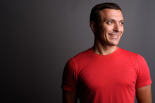 Man Wearing Red Shirt Against Gray Background
